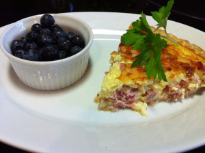 A slice of Ham and Swiss Quiche with a side of fresh Blueberries (Photo Credit: Adroit Ideals)
