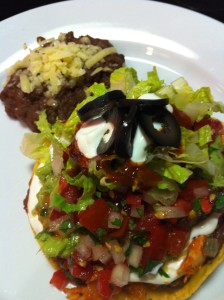 Chipotle Chicken Tostada topped with cheeses, lettuce, pico de gallo, guacamole, sour cream, and black olives .  Side of Refried Black Beans (Photo Credit: Adroit Ideals)