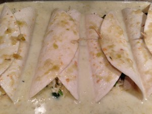 Sauced and filled chicken and spinach enchiladas ready for the oven (Photo Credit: Adroit Ideals)