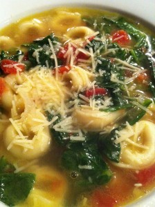 Tortellini Soup with Spinach and Tomato sprinkled with Parmesan (Photo Credit: Adroit Ideals)