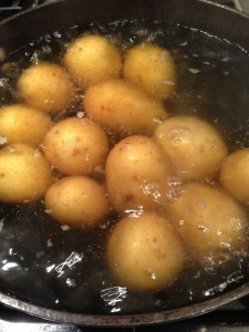 Golden potatoes simmering in water (Photo Credit: Adroit Ideals)