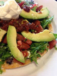 Tex Mex Tortilla Pizza: Gooey black beans and cheese on a tortilla topped with an arugula/tomato salad! (Photo Credit: Adroit Ideals)