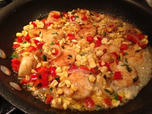 Seared scallops along with corn, red bell pepper, shallots, and parsley.  (Photo Credit: Adroit Ideals)
