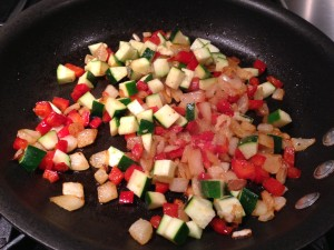 Diced Zucchini, red bell pepper, and onion are sauteing together.  (Photo Credit: Adroit Ideals)