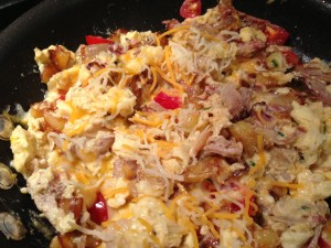 Add the shredded cheese to the pulled smoked pork scramble (Photo Credit: Adroit Ideals)