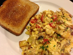 Pulled Smoked Pork Scramble with Yukon Gold potatoes, onions, grape tomatoes, chives, eggs, cheese, and pulled smoked pork (Photo Credit: Adroit Ideals)