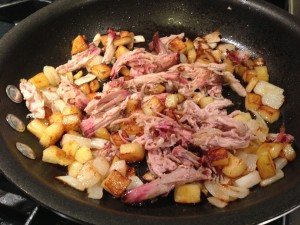 Add the pulled smoked pork to the potatoes and onions (Photo Credit: Adroit Ideals)