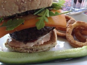 Grass fed beef burger with smoked cheddar, arugula, tomato and special sauce on a sesame bun served with onion rings and homemade dill pickles (Photo Credit: Adroit Ideals)