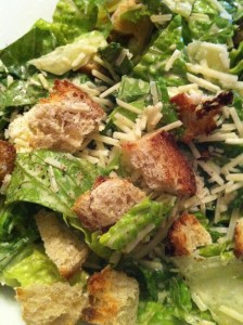 My husband's Caesar dressing on a salad of Romaine lettuce, shredded Parmesan, and toasted baguette croutons (Photo Credit: Adroit Ideals)