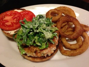 Salmon burger served with lettuce, tomato, and mayo.  Onion rings on the side.  (Photo Credit: Adroit Ideals)