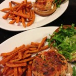 Salmon burgers with spinach and feta on wheat buns with garlic aioli and shredded Romaine.  Served with sweet potato fries.  (Photo Credit: Adroit Ideals)