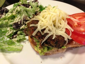 Veggie black bean burger with shredded Monterey Jack, tomato, and lettuce.  Served with a side of Caesar salad. (Photo Credit: Adroit Ideals)
