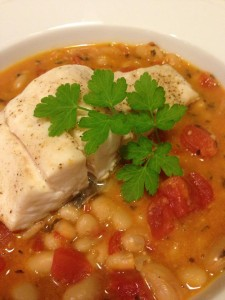 Grilled white fish served over a garlicky white bean and tomato stew (Photo Credit: Adroit Ideals)