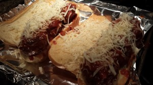 Sprinkle the meatball sandwiches with shredded mozzarella and parmesan cheeses (Photo Credit: Adroit Ideals)