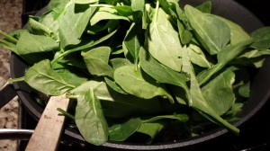 Add the fresh spinach leaves to the garlic and shallot mixture (Photo Credit: Adroit Ideals)