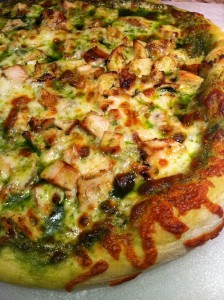 Pizza smothered in chicken, pesto, and cheese (Photo Credit: Adroit Ideals)