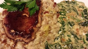 Seared pork chops in a sherry sauce served over a rice medley and accompanied by garlicky creamed spinach and arugula (Photo Credit: Adroit Ideals)
