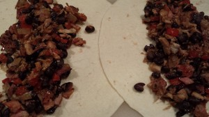 Place the smoked pork and black bean filling down the middle of each flour tortilla (Photo Credit: Adroit Ideals)