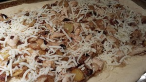 Shredded mozzarella covers chicken, roasted garlic cloves, and sauteed fingerling potatoes on a pizza crust ready for the oven (Photo Credit: Adroit Ideals)