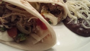 Smoked Pork Tacos with Monterey Jack Cheese and Pico de Gallo.  Side of Refried Black Beans. (Photo Credit: Adroit Ideals)