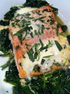 Elegant Baked Salmon with Creamy Citrus Herb Sauce over sauteed Spinach (Photo Credit: Adroit Ideals)