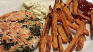 Homemade tartar sauce accompanies sockeye salmon burgers served with sweet potato fries (Photo Credit: Adroit Ideals)