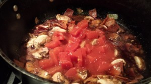 Add the red wine and diced tomatoes and simmer.  (Photo Credit: Adroit Ideals)