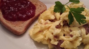 Homemade Strawberry Jam on Multigrain Toast accompanies Scrambled Eggs with Melty Brie and Crispy Prosciutto (Photo Credit: Adroit Ideals)