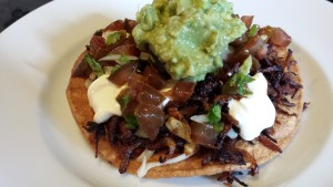 Serve the pork carnitas on a crispy tostada with all the fixin's! (Photo Credit: Adroit Ideals)