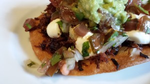 Pork Carnitas served on crispy tostadas with pico de gallo, sour cream, and guacamole (Photo Credit: Adroit Ideals)
