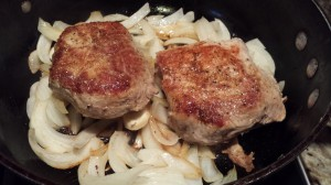 Add onions to the pan then add the pork on top (Photo Credit: Adroit Ideals)