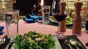 A green salad with crispy croutons, glass of wine, and a fire in the fireplace (Photo Credit: Adroit Ideals)