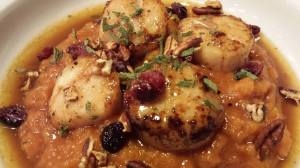 Seared scallops over pumpkin butternut squash puree draped with Calvados sauce and garnished with toasted pecans, dried cranberries, fresh chopped sage, and crispy crumbled bacon (Photo Credit: Adroit Ideals)
