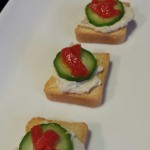 Smoked White Fish Salad Mini Toasts with a Mini Cucumber Slice and Sliver of Roasted Red Bell Pepper (Photo Credit: Adroit Ideals)