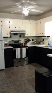 "The kitchen ""AFTER"" photo.  I love the black paint on the bottom cabinets! (Photo Credit: Adroit Ideals)"