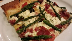 A slice of prosciutto, asparagus, and ricotta pizza (Photo Credit: Adroit Ideals)