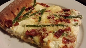 A slice of prosciutto asparagus ricotta pizza with parmesan! (Photo Credit: Adroit Ideals)