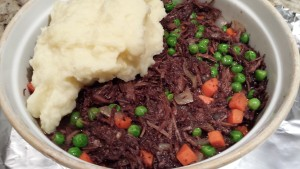 Spoon the mashed potatoes over the beef mixture  (Photo Credit: Adroit Ideals)