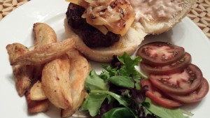The Best Burger with sharp cheddar cheese, grilled onions, sliced tomato, baby lettuces and my Special Sauce.  Served with oven-roasted rosemary garlic potato fries.  (Photo Credit: Adroit Ideals)