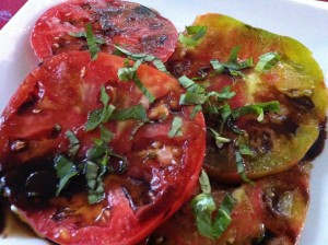 Sliced ripe heirloom tomatoes drizzled with balsamic syrup and topped with basil chiffonade (Photo Credit: Adroit Ideals)