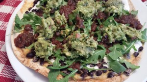 Tortilla Pizza with Homemade Guacamole over Arugula (Photo Credit: Adroit Ideals)