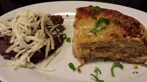 slice of baked enchilada stack along with refried beans