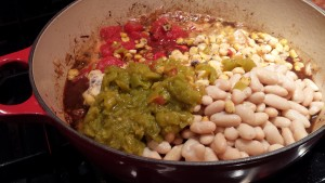 Add the beans, corn, diced tomatoes, green chiles, and chicken stock (Photo Credit: Adroit Ideals)