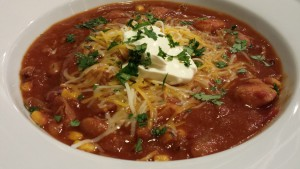 Red Chicken Chili with Guinness Beer topped with Cheeses, Sour Cream, and Cilantro (Photo Credit: Adroit Ideals)