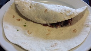 Fold the tortilla edge over the filling (Photo Credit: Adroit Ideals)
