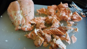 Flake the baked salmon into smaller pieces with a fork (Photo Credit: Adroit Ideals)