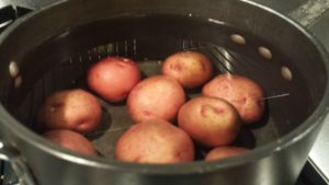 Boil some potatoes in water in a pot (Photo Credit: Adroit Ideals)