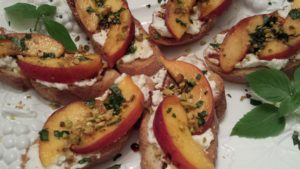 Sliced Peaches, Pistachios, and Ricotta decorate Toasted Baguettes as an elegant appetizer (Photo Credit: Adroit Ideals)