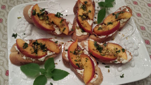 Ripe peach slices over ricotta-slathered toasted baguette crowned with chopped toasted pistachios, cinnamon basil chiffonade and a touch of honey. (Photo Credit: Adroit Ideals)
