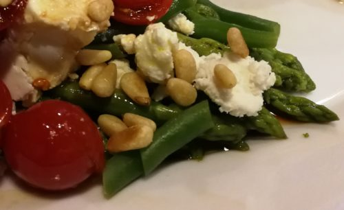A close up of my Herbed Asparagus Green Bean Tomato Salad with creamy goat cheese and toasted pine nuts